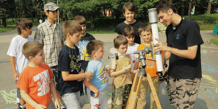 Children learning how to use a telescope at a Universe Awareness activity in Romania. Credit: Universe Awareness