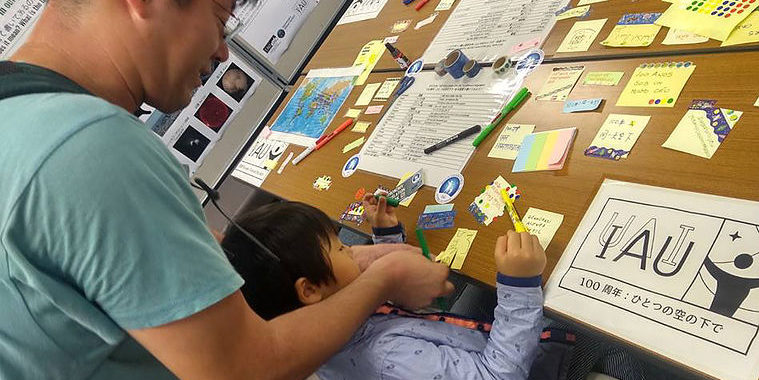 "Father helps his son writing IAU100 slogan ""100 years: under one sky"" in Japanese. Credit: ATN / IAU OAO."