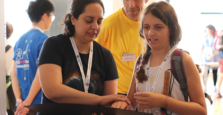 A young girl feels a tactile model developed for blind students at the Inspiring Stars Exhibition in Vienna. Credit: Hannah Harris